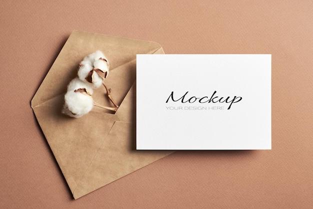 Biglietto di auguri mockup stazionario e busta artigianale con fiore di cotone asciutto all'interno