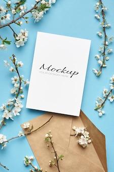 Biglietto di auguri mockup stazionario con busta e ramoscelli di fiori di ciliegio