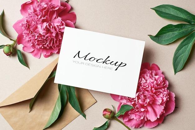 Modello stazionario di biglietto di auguri con busta e fiori di peonia rosa
