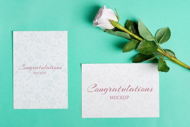 Biglietto di auguri con bellissimi fogli di carta bianca e fiore rosa mockup