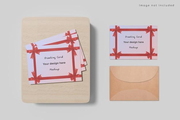Biglietto di auguri con mockup di busta su tavola di legno