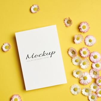 Mockup di auguri o invito o carta con fiori margherita su giallo