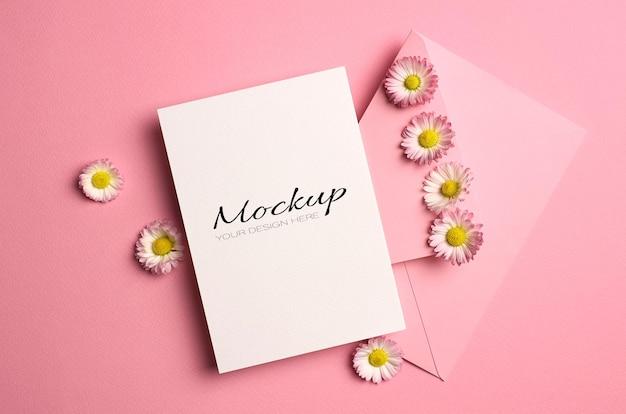 Mockup di auguri o invito o biglietto con busta e fiori margherita su rosa Psd Premium
