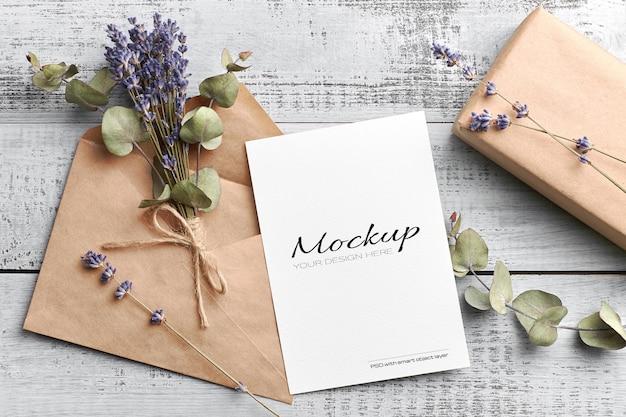 Mockup di biglietto di auguri o invito con busta, confezione regalo e bouquet di lavanda secca con eucalipto