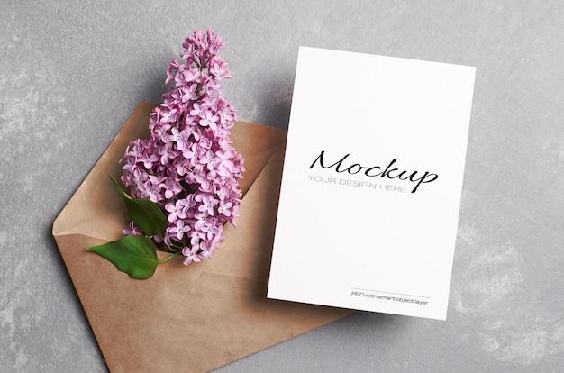Modello di biglietto di auguri o invito con busta con fiori lilla su grigio