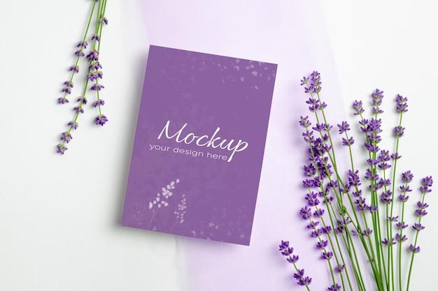 Modello di biglietto di auguri o invito con fiori di lavanda freschi su bianco