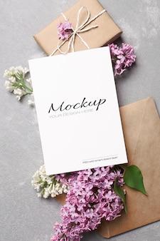 Modello di biglietto di auguri o invito con confezione regalo, busta e fiori lilla primaverili