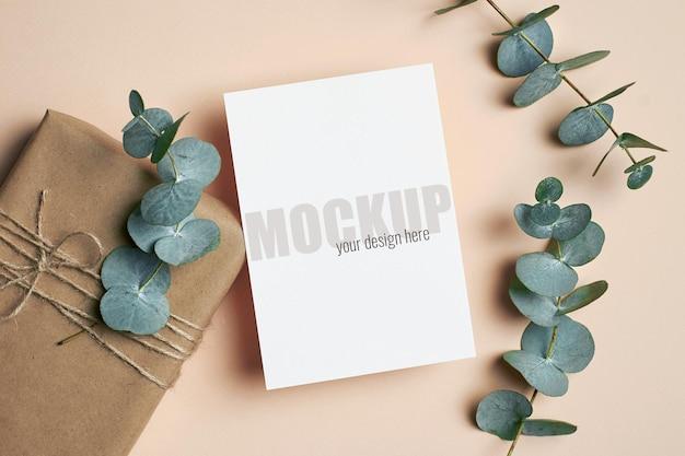 Modello di biglietto di auguri o invito con confezione regalo e ramoscelli di eucalipto verde