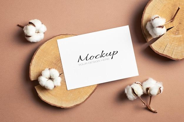 Mockup di biglietti di auguri o di invito con ceppo tagliato in legno e decorazioni di fiori di cotone