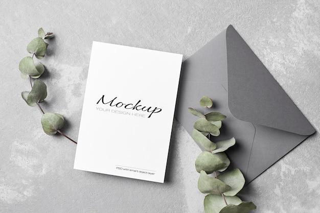Mockup di biglietto di auguri o invito a nozze con busta e ramoscello di eucalipto secco