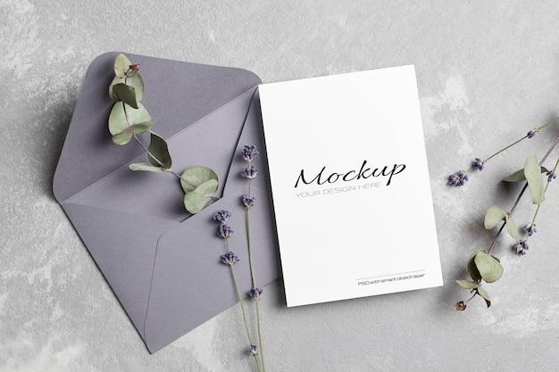 Mockup di biglietto di auguri o invito a nozze con busta, lavanda e rametti di eucalipto secchi