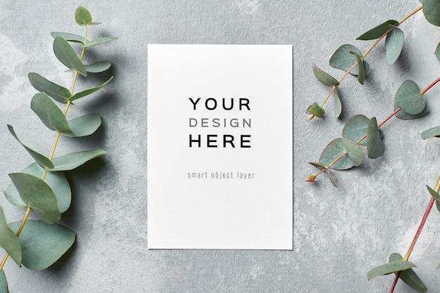 Mockup di carta di auguri e invito a nozze con ramoscelli di eucalipto freschi