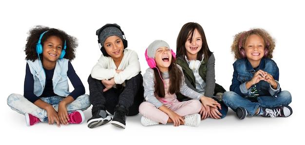 Gruppo di bambini studio sorridente indossando le cuffie e abiti invernali