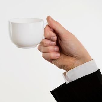 Mano che tiene un mock-up di tazza
