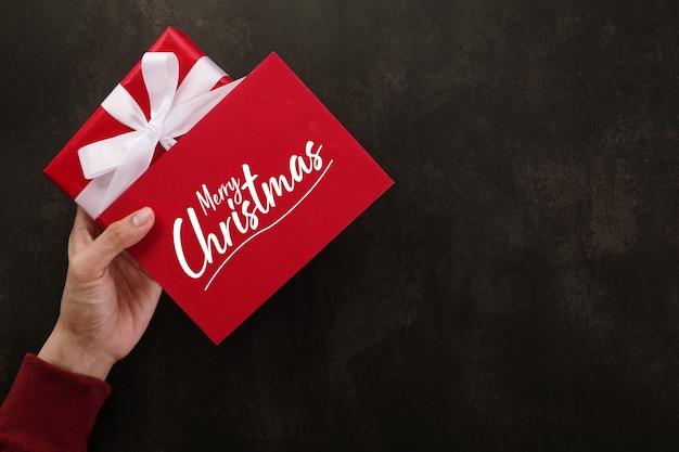 Mani che tengono il modello di mockup della cartolina d'auguri di buon natale e la confezione regalo.