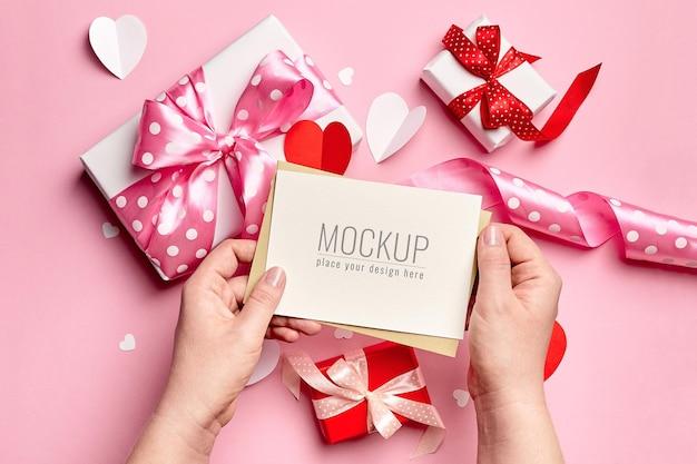 Mani che tengono il mockup di carta di san valentino con scatole regalo e cuori di carta