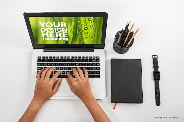 Mani che scrivono sul computer portatile allo spazio di lavoro sul modello bianco del fondo