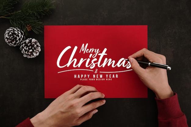 Mani che scrivono mockup di cartolina d'auguri di buon natale