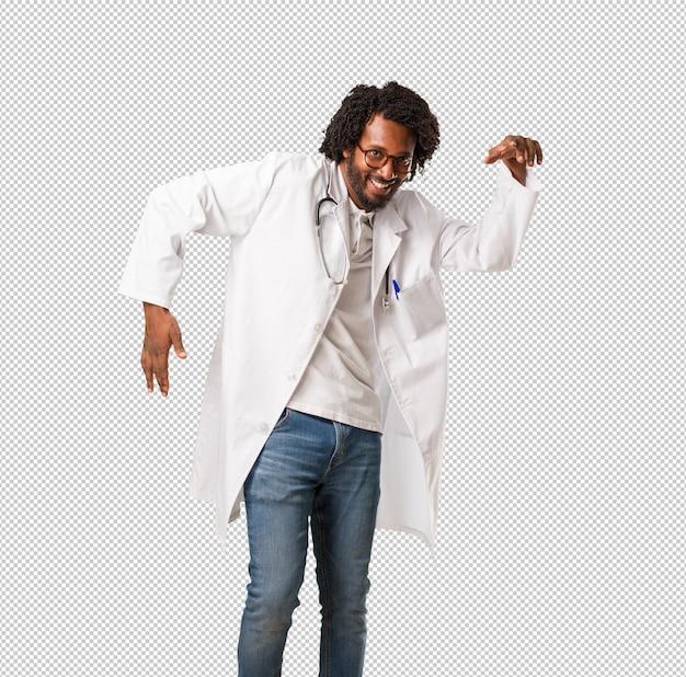 Medico afroamericano bello che ascolta la musica, ballando e divertendosi, muovendosi, gridando ed esprimendo felicità, libertà