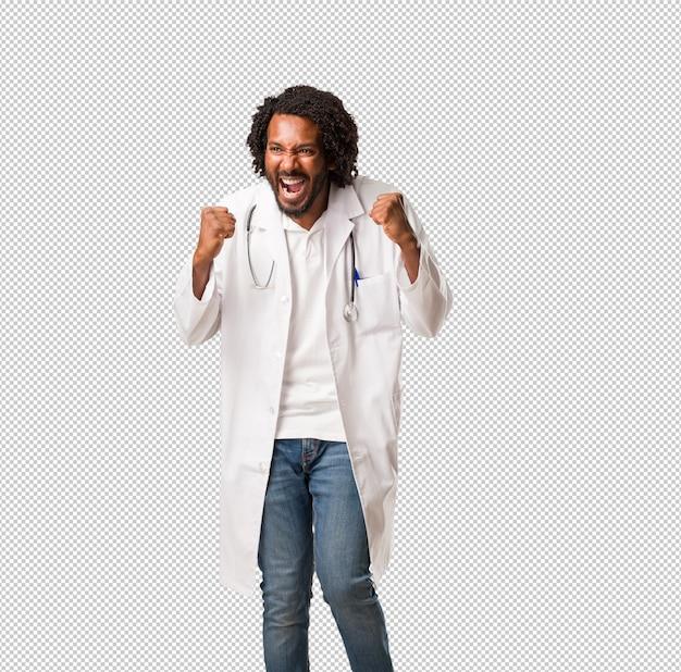 Medico afroamericano bello molto felice ed eccitato, alzando le braccia, celebrando una vittoria o un successo, vincendo alla lotteria