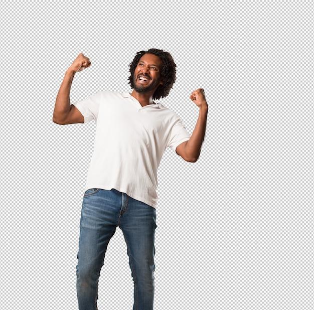 Bello afroamericano molto felice ed eccitato, alzando le braccia, celebrando una vittoria o un successo, vincendo alla lotteria
