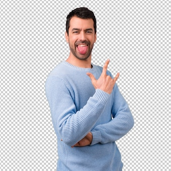 Uomo bello che mostra lingua alla macchina fotografica che ha sguardo divertente
