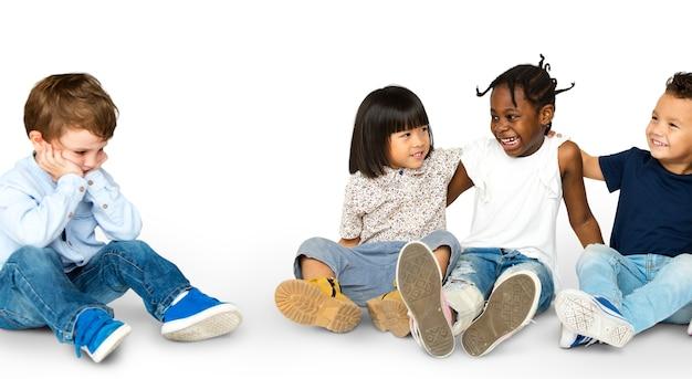 Gruppo di felicità di bambini adorabili e adorabili e un ragazzo solitario