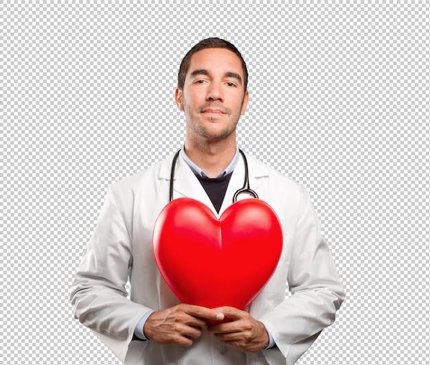 Medico felice che tiene un cuore del giocattolo contro fondo bianco