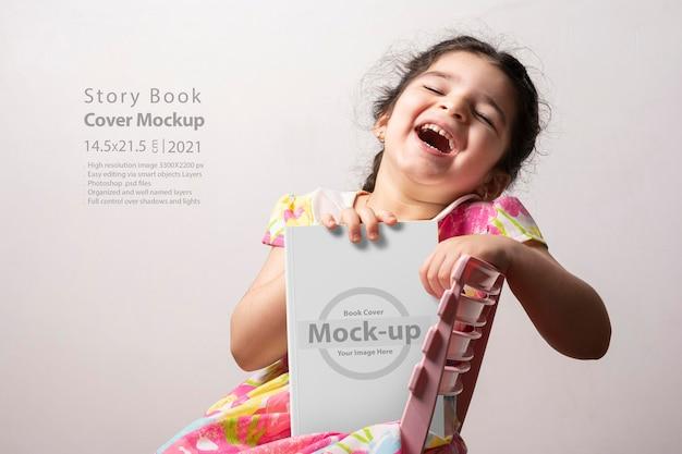 Bambina felice che tiene un libro di storia divertente con copertina vuota nella parte anteriore del corpo