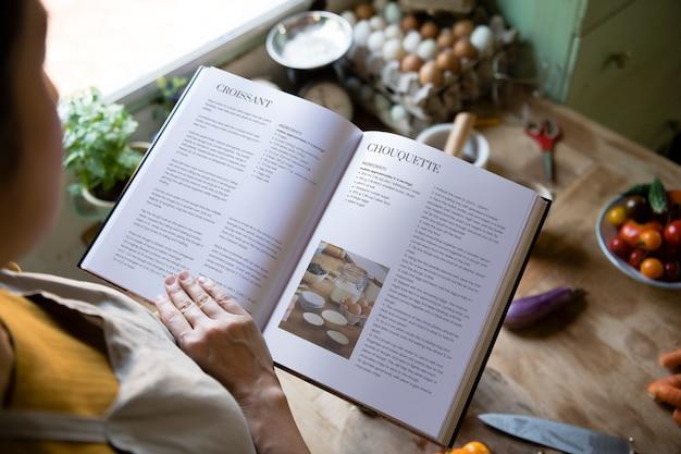 Donna felice che legge un libro di cucina in cucina