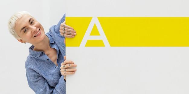 Donna felice che sgattaiola fuori un mockup di muro