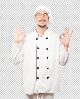 Felice giovane chef facendo un gesto di meditazione