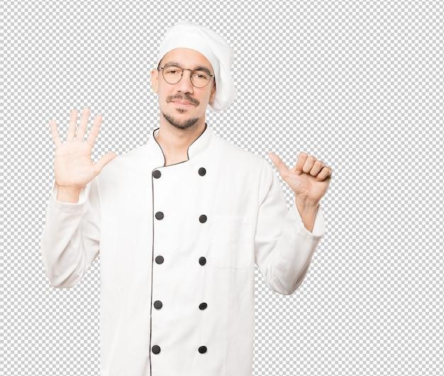 Felice giovane chef facendo un gesto numero sei con le mani