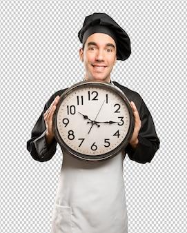 Felice giovane chef utilizzando un orologio