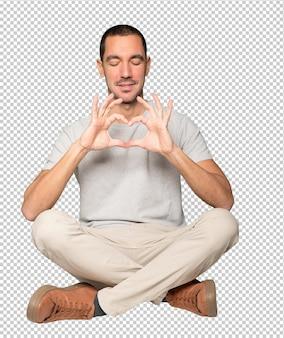 Felice giovane uomo che fa un gesto d'amore con le sue mani