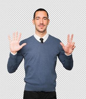 Giovane felice che fa un gesto di numero otto con le sue mani
