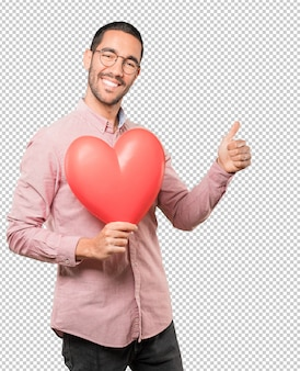 Giovane felice che tiene un grande cuore del giocattolo e che fa i gesti circa il san valentino