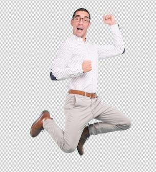 Giovane felice che salta con un gesto della celebrazione - colpo pieno del corpo