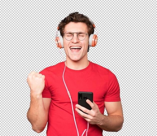 Felice giovane uomo che fa un gesto di celebrare. utilizzando le cuffie e tenendo in mano uno smartphone