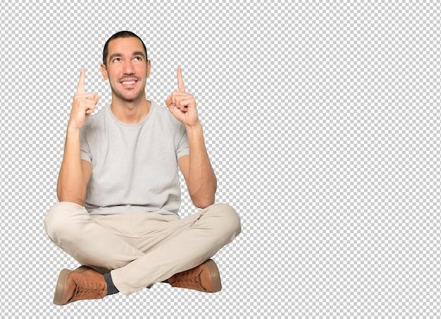 Felice giovane uomo rivolto verso l'alto con il dito