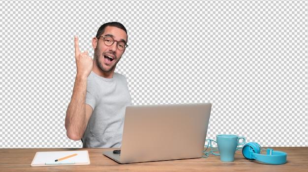 Felice giovane uomo seduto alla sua scrivania e facendo un gesto del numero uno