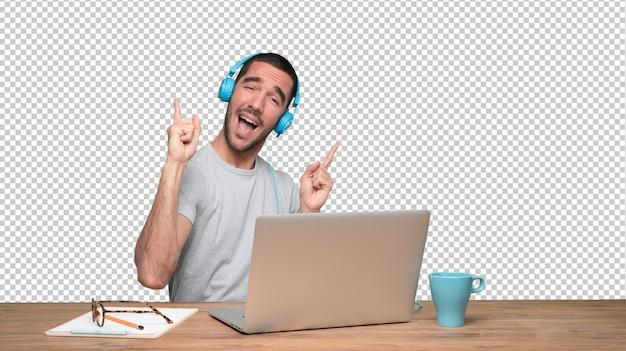 Felice giovane uomo seduto alla sua scrivania e utilizzando una cuffia