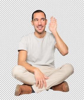 Felice giovane uomo sorridente e facendo un gesto di provare a sentire qualcosa