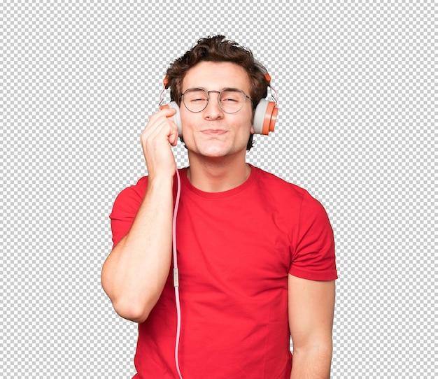 Felice giovane uomo utilizzando le cuffie e uno smartphone e facendo un gesto di denaro