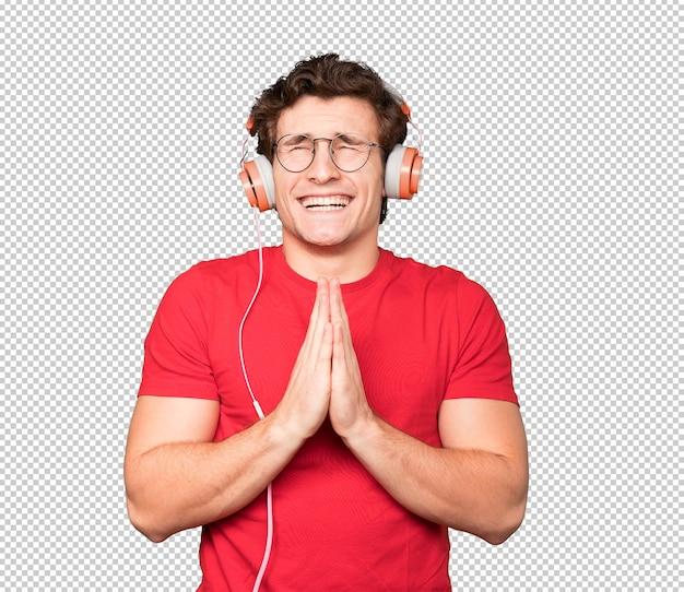 Felice giovane uomo utilizzando le cuffie e uno smartphone e facendo un gesto di preghiera