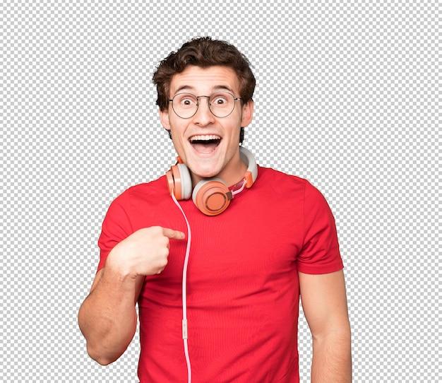 Felice giovane uomo utilizzando le cuffie e uno smartphone e indicando se stesso con il dito