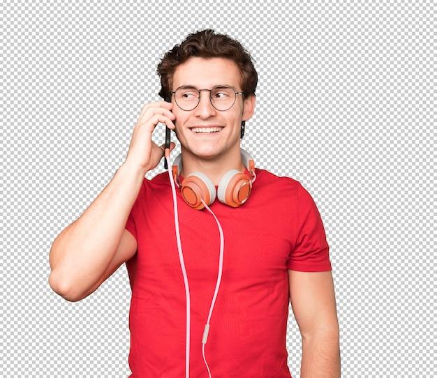 Felice giovane uomo utilizzando le cuffie e uno smartphone