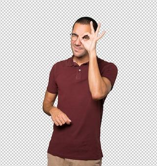 Felice giovane che usa le mani come un binocolo
