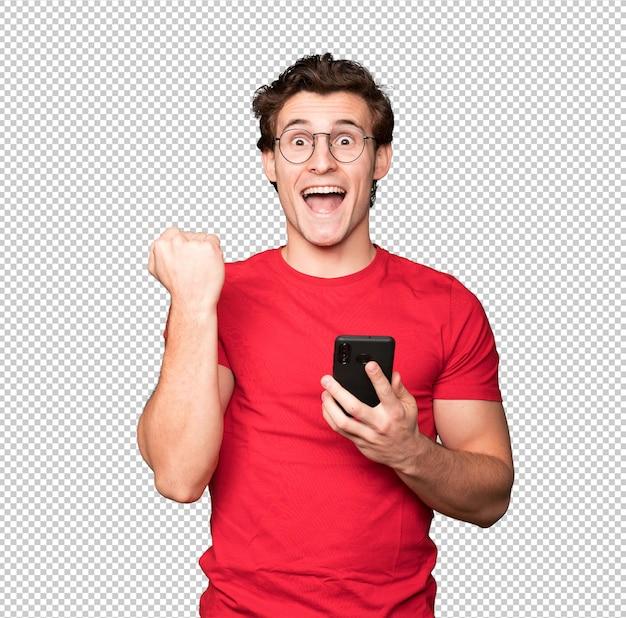 Felice giovane uomo utilizzando un telefono cellulare e celebrando