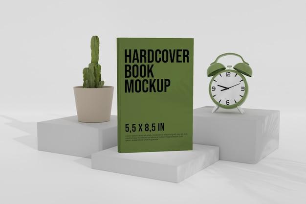 Mockup di libro con copertina rigida sul podio con orologio analogico